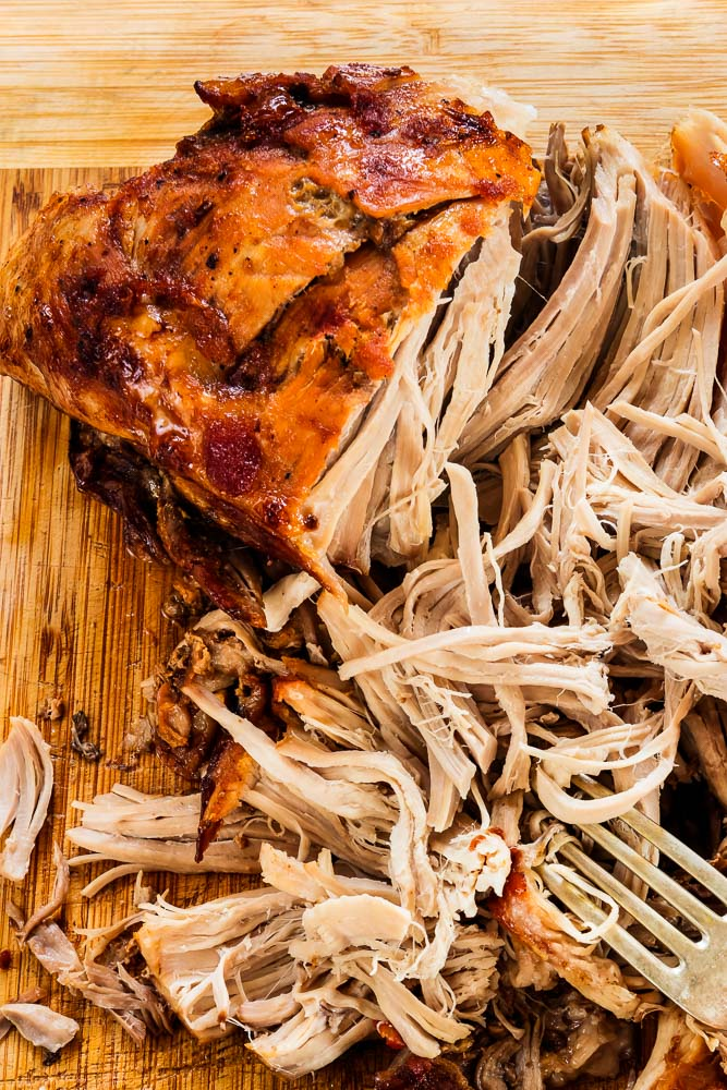 pulled pork on a cutting board with two forks and half of the roast ready to be pulled