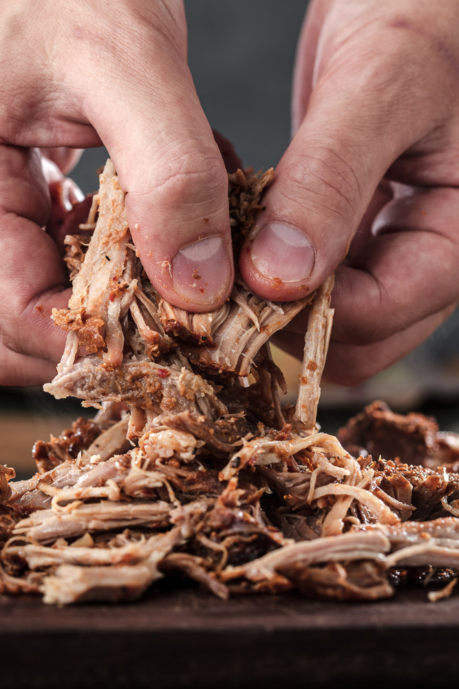 a person shredding instant pot pulled pork with their hands