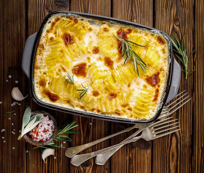Instant Pot scalloped potatoes on a wood table with three forks