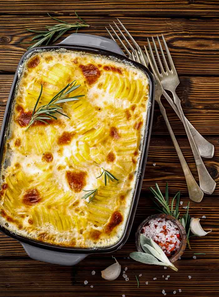 Instant Pot scalloped potatoes on a wood table with three forks and a small dish of coarse salt
