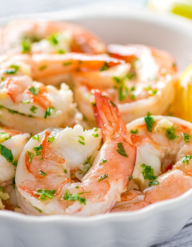 instant pot shrimp scampi in a white bowl with a lemon wedge