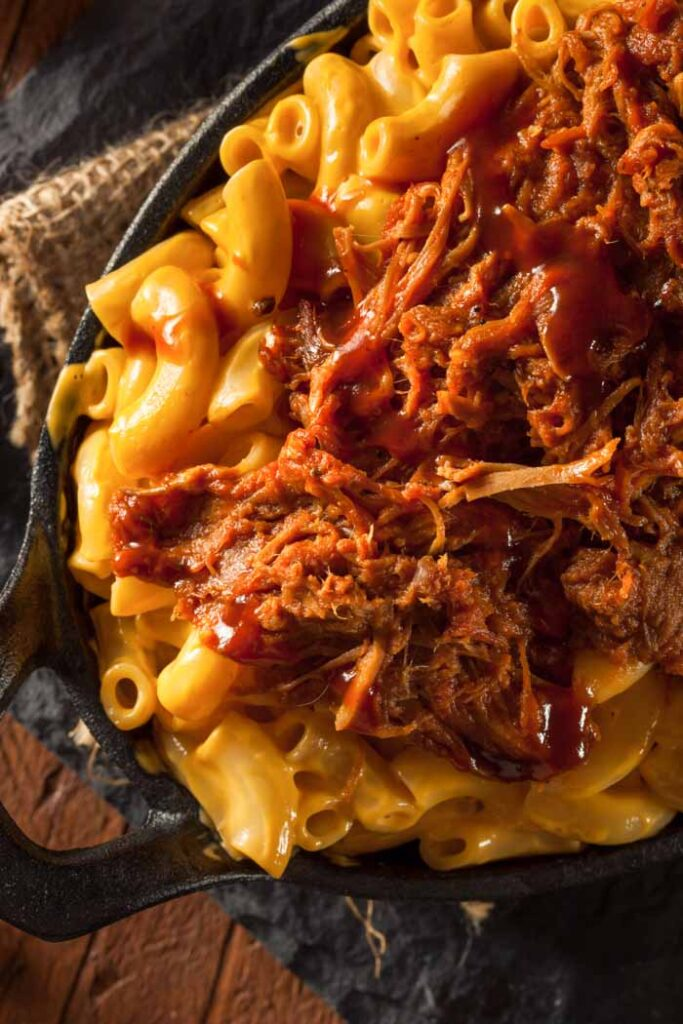 Pulled pork mac and cheese in an oval cast iron skillet