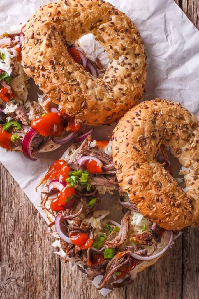 Two sliced bagels on parchment paper set on a wood table, topped with instant pot pulled pork and chopped red onion and bell pepper