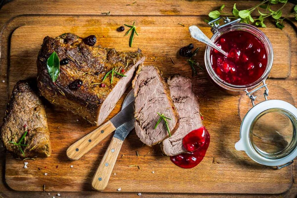 sliced instant pot venison roast on a cutting board with two knives and a jar of cranberry sauce