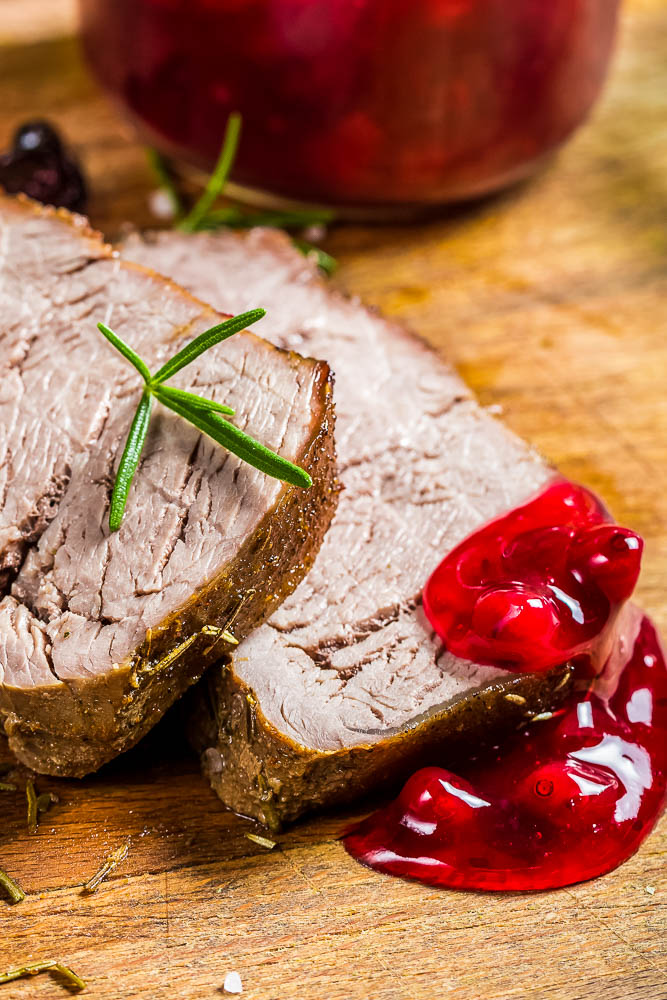 a closeup photo of two slices of instant pot venison roast with cranberry sauce