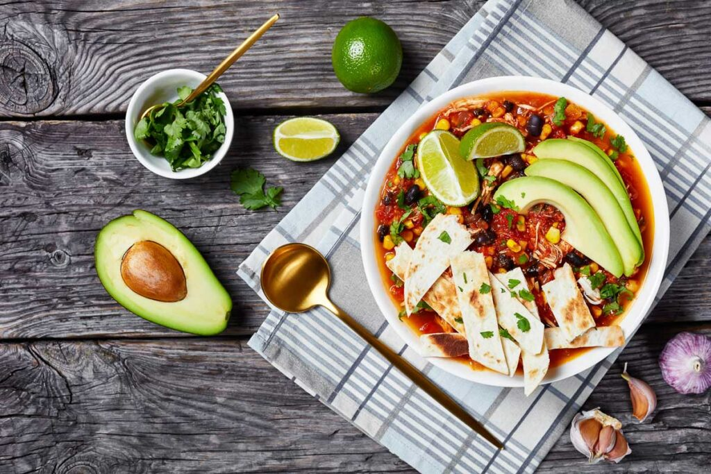 a bowl of instant pot taco soup topped with homemade tortilla chips, avocado slices, and fresh lime wedges, next to lime wedges, a halved avocado and a small dish of chopped cilantro